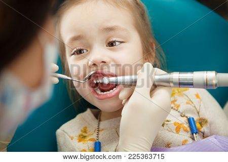 Child in comfortable chair calmly goes through procedure of teeth polishing by professional dentist that holds modern electrical tool. Cosmetic procedure for oral cavity.