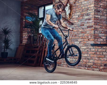 Caucasian man makes an acrobatic figure with BMX in a studio. Studio shot.