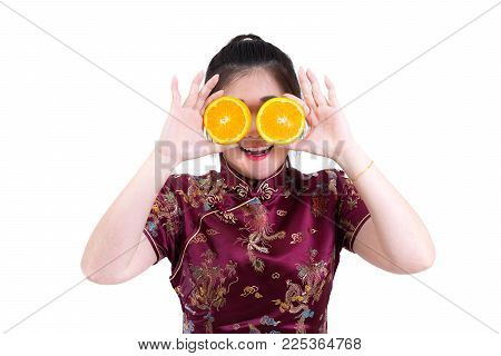 Portrait of asian woman in traditional chinese long dress, cheongsam, presenting oranges on hand for healthy Chinese New Year concept, healthy eating