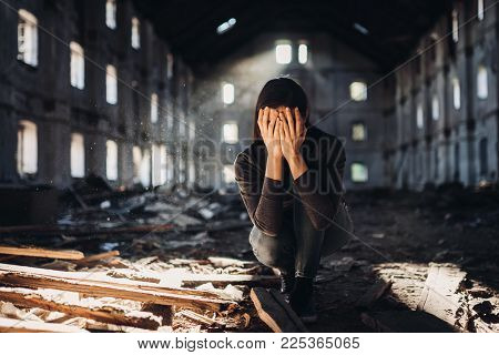 Sad depressed person in abandoned destroyed building crying.Emotional portrait.Raped woman victim of domestic violence.Human trafficking and kidnapping.Scared and worried woman. Forced into problem.