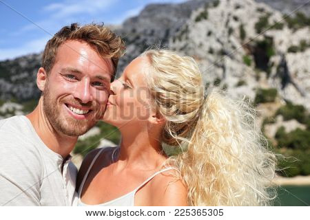 Happy summer travel couple selfie girl kissing boyfriend in love. Young lovers people lifestyle. Blonde woman giving cute kiss to man for photo.