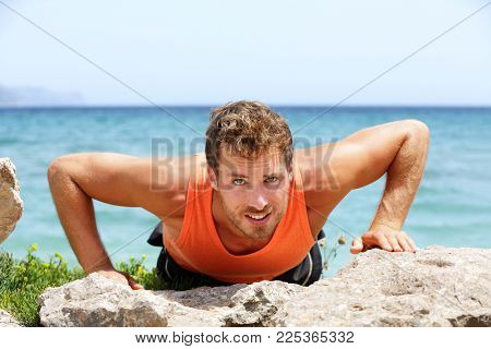Fit man doing push-ups in summer beach outdoor. Athlete training muscles doing push up exercises outdoors. Healthy lifestyle concept. Fitness lifestyle.