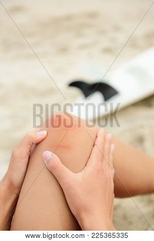Sport injury - painful knee wound surfing accident. Young woman surfer holding knee in pain after surfboard surf injury and bruises. Blue and red effect to enhance the medical condition.