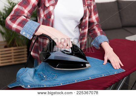 Partial View Of Woman Ironing Clothes At Home