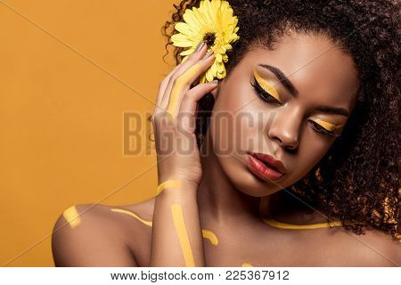 Beautiful African American Woman With Artistic Make-up And Gerbera In Hair Dreaming Isolated On Oran
