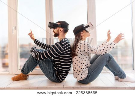 Great time. Earnest loving attractive couple resting on windowsill while using VR glasses and gesturing