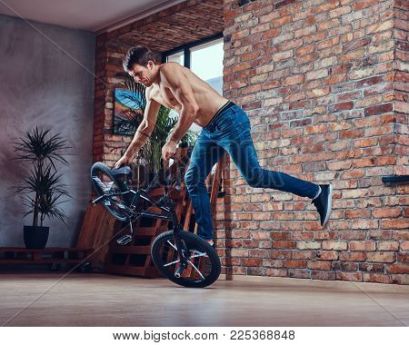 Strong shirtless man makes an acrobatic figure with BMX in a studio. Studio shot.