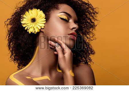 Young Sensual African American Woman With Artistic Make-up And Gerbera In Hair Tenderly Touches Her