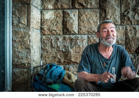 Happy and smiling poor homeless man sitting in the shadow of the building on the urban street in the city and drinking alcohol drink from small bottle