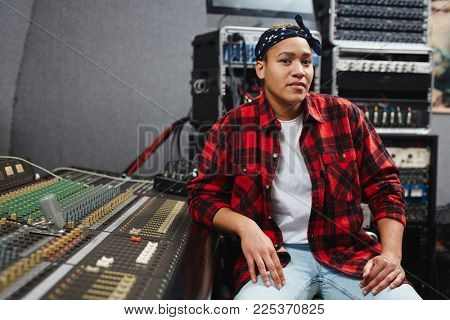 Young sound operator sitting by soundboard in her record studio