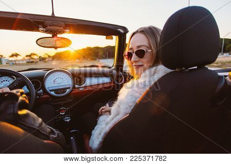 Beautiful and stylish young woman big fake fur coat and vintage sunglasses with blonde hair sits in cabriolet convertible car with open roof, smiles and poses for fashion shoot on sunset