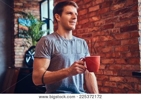 A stylish tattoed attractive man dressed in jeans and a t-shirt, sitting on a wooden chair, holding a cup of coffee. Looking away.
