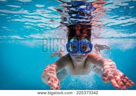 Boy in mask dive in swimming pool, underwater shoot