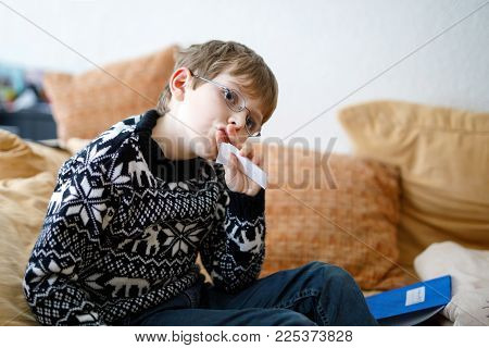 Tired little kid boy with glasses at home making homework at the morning before the school starts. Little child learning multiplication tables and basics indoors. Elementary school and education