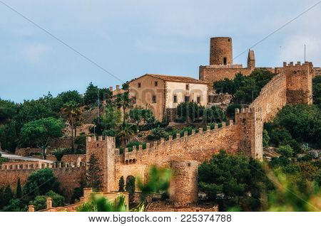 Capdepera castle on green hill in Mallorca island, Spain. Beautiful landscape with medieval architecture in Majorca