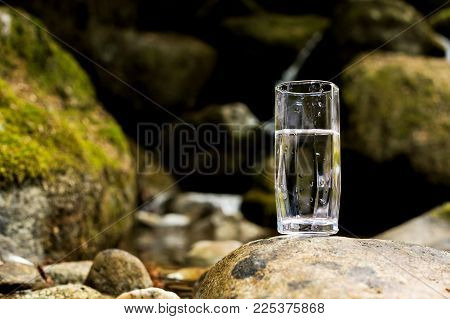 A transparent glass glass with mineral mountain river water stands on a stone beside the mountain river creek against a background of stones covered with green moss. The concept of drinking clean water. Production of mineral water. Natural products