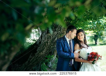 Horizontal Sensitive Portrait Of The Newlyweds Smiling, Tenderly Hugging And Looking At Each Other U