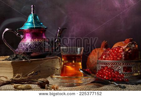 Turkish tea, the teapot is on a big book, there is steam, a national Turkish cup with tea and a vase with a ripe garnet