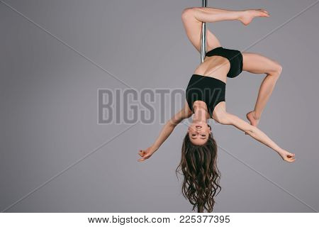Upside Down Of Beautiful Sporty Girl Exercising With Pole And Looking At Camera On Grey