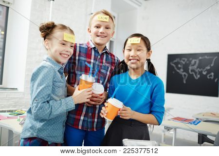 Laughing classmates with drinks playing name game during lunch break in school