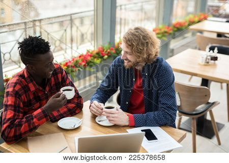 Intercultural young men sitting in cafe and having business talk by cup of tea