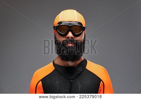 Close-up portrait of a bearded male in orange neoprene diving suit and dive mask isolated on grey background.