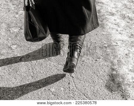 Female legs in black winter boots walking down the street. Female legs. Black winter boots.