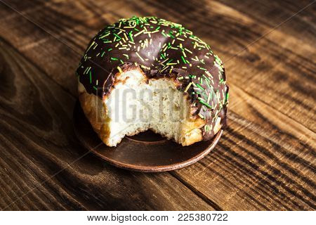 a bitten donut with chocolate on a wooden background