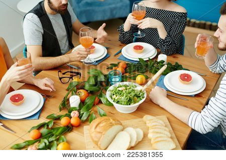 Group of vegetarians sitting by festive table with healthy food and having talk