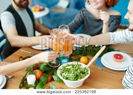 Human hands clinking by glasses of fruit juice during vegetarian festive dinner