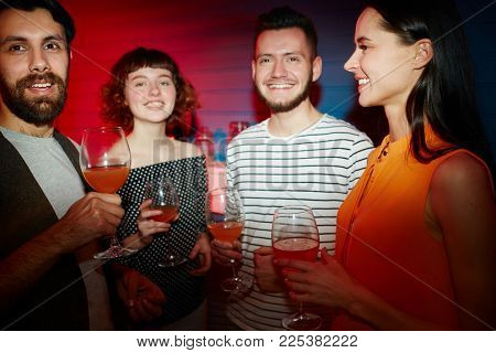Group of happy young friends with drinks gathered for party in night club