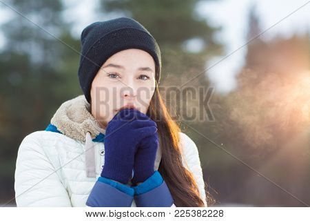 Freezing young female in beanie and gloves warming her hands while keeping them by mouth on winery day