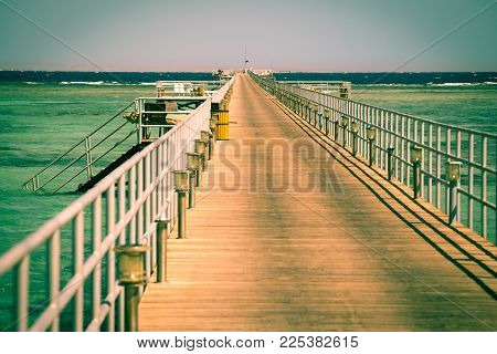 Long pier with azure water in Red sea, resort concept in Egypt, vintage toned image