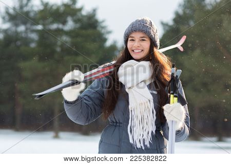 Smiling girl in grey knitted beanie, white scarf and fluffy mittens holding skis and sticks