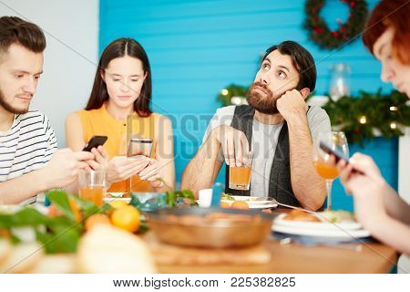 Bored guy with glass of juice sitting by served dinner table among his friends searching in their gadgets