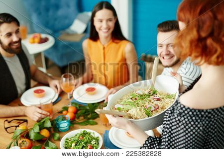 Young friends waiting for housewife bringing homemade food for festive dinner