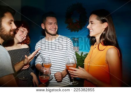 Happy young friends with refreshing drinks enjoying talk at party in club or restaurant