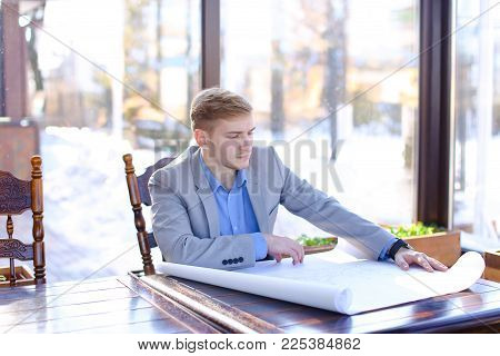 Young Businessman Sitting At Cafe Table And Checking Project. Blonde Man Wearing Smart Watch. Concep