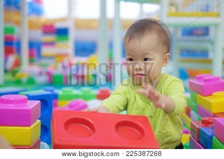 Cute little Asian 18 months / 1 year old toddler baby boy child wearing green sweater having fun playing with big colorful plastic blocks indoor, Educational toys for young children concept