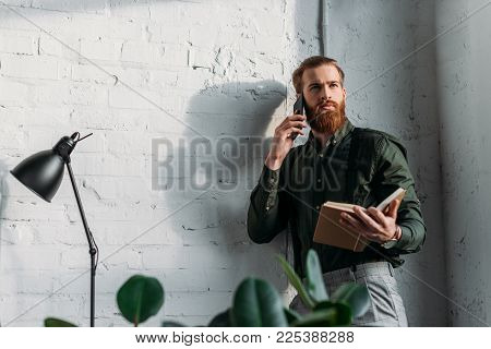 Businessman Talking By Smartphone, Holding Book And Looking Away