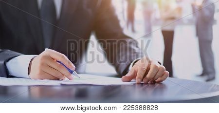 Close-up of human hand writing on paper on team work background