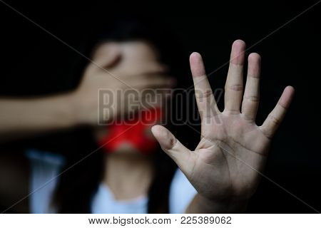 Woman hand sign for stop abusing violence, another hand close eyes and wrapping her mount by adhesive red tape, Human Rights Day concept.