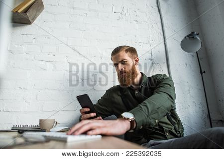 handsome bearded businessman looking at smartphone in office poster
