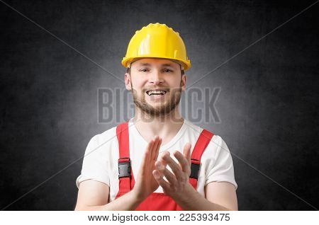 Happy, smiling construction worker clapping his hands