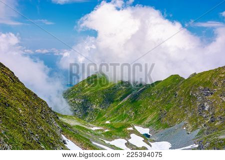 Valley Of Fagaras Mountains In Clouds. Beautiful Summer Landscape With Rocky Cliffs And Grassy Slope