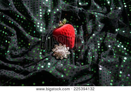 Silwer Brooch Next To Red Strawberry On Green Texture.