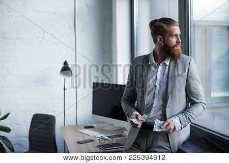 View Of Businessman Holding Dollars And Looking Away