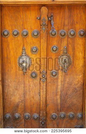 SHIRAZ, IRAN - JUNE 17, 2007: Exterior of a house entrance with the vintage metal door handles in Shiraz, Iran.