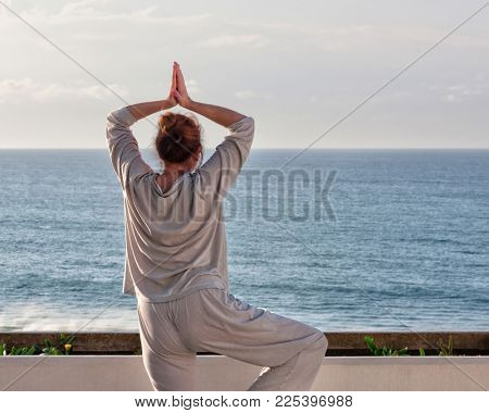 Middle age woman standing on the terrace practicing Qigong and yoga exercises, view of the Pacific ocean, Durban