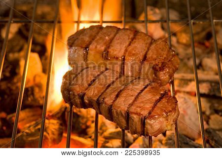 Grilled Steak over a grill with flames